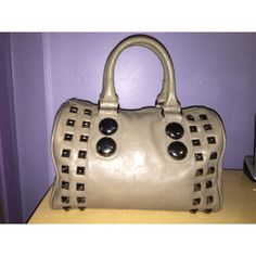 Studded Handbag Mauve colored leather bag with grayish silver stud accents. Gently worn. Larger circular studs have minor scratches from wear, otherwise in really good condition. All zippers are fully functional. Two zippered pockets inside, one being a divider and two open compartments for cell phone or other miscellaneous items. Also includes crossbody strap which has never been used. ALDO Bags
