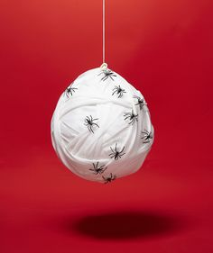 A skin-crawling addition to any dark corner. Use a funnel to fill a white balloon with a handful of rice, then inflate until three-quarters full and tie closed. Affix the end of a gauze roll near the knot with a double-sided adhesive and unravel irregularly around the balloon until completely covered (it may take 2 to 3 rolls). With the adhesive, secure each gauze end and attach a few plastic spiders. Tie twine around the knot and hang.