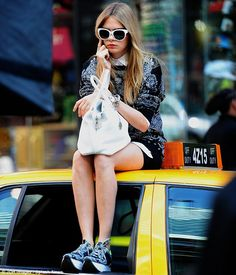 Bored? Cara was also seen on her mobile phone as she sat on the top of a yellow taxi cab as part of the shoot