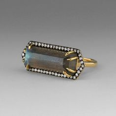 An 18k yellow gold, emerald cut labradorite bar ring wtih blackened pave diamond border=.37cttw. Made By Jemma Wynne