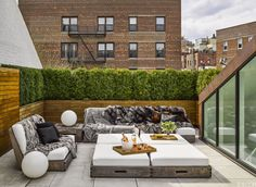 A boxwood hedge shields Jeffrey Kalinsky's roof terrace; the teak furniture by David Sutherland has cushions covered in a Perennials fabric.