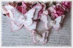 Each butterfly is doubled layered with a little rose embellishment. The script image was hand stamped to the butterflies and the edges inked  . Each butterfly has three different types of glitter and was sprinkled with micro beads. So, they have all the shimmer and shine to really catch the eye! The antennas are made from wire and adhered with a foam dot for dimension. Gently lift the layered wings for even more dimension.