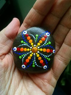 Hand Painted Beach stone from the shores of Lake Erie  by Miranda Pitrone  Rainbow Dot Art Flower Size: approx. 2 inch diameter  Colors: White,Red, Tangerine Orange, Pale Green, Grasshopper Green Pale Yellow, Magenta, Pale Blue, Turquoise Blue, Violet, Purple  Shape: Round-ish Medium: Water-based Acrylics  Sealed/Protectant: Yes. with Indoor/Outdoor UV protectant Varnish - Gloss  Style: Mandala, Rings, Flower Technique: Pointillism, Dotillism, dot art  Put some color in your life or someone…