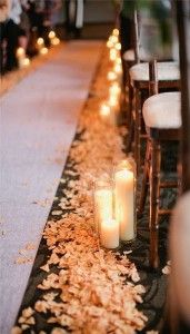 Floating candles make the perfect aisle pews. It transforms the room into an indoor elegant ceremony with light orange rose pedals on each side of the aisle. You can also use, cream colored, caramel, or light pink flowers as well. Coordinates extremely well for a autumn wedding.