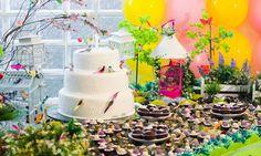 Mesa com bolo e docinhos para uma festa infantil.