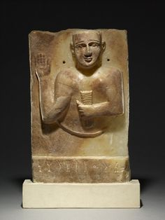 Rectangular calcite-alabaster stela with bust in relief of woman holding ears of corn in her left hand, and right hand raised; wearing a round-topped short-sleeved dress, apparently unpatterned, and a pair of bracelets on each wrist; ears pierced for presumed attachment of metal earrings, now lost; single line of South Arabian inscription in Qatabanian across the low stepped base relating to Kariat (of clan) Dharhan; top partially burnt in antiquity.
