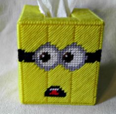 """Up for sale is a plastic canvas tissue box cover/Kleenex cozy featuring 4 Minions inspired by """"Despicable Me.""""  Each of the box's 4 sides has a slightly different style of Minion.  This Kleenex cozy fits a standard, boutique size tissue box (cube style).  This plastic canvas kleenex cover i..."""