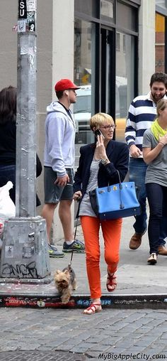 A neon Orange pair of jeans, a striped shirt under a navy blazer and a blue handbag. That is a way to walk your dog with style on the streets of SoHo.