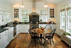 3 things I need from this kitchen: wood floors, schoolhouse lights, apron front sink... ohhh make that 4.... windows!