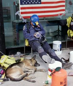 A police officer and his K-9 partner get much needed rest during the rescue efforts of 9/11.
