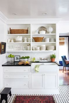 White kitchen - dark countertop - patterned tile floor - antique rug - open shelving - kitchen styling