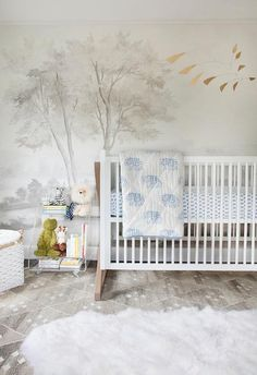 Exquisite boy's nursery features a an accent wall clad in Susan Harter Muralpapers Calmsden in Grisaille lined with a ducduc Campaign Crib dressed in a Rikshaw Design Toddler Quilt, Taj Blue Crib Sheet and Crib Sheet Booti Blue under an Etsy Abstract Brass Mobile atop a Safavieh Natural Kilim Dhurrie Natural & Ivory Area Rug.