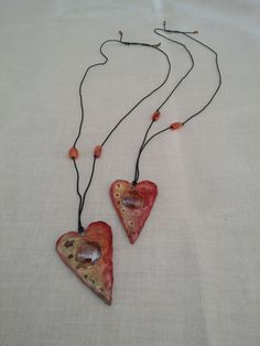 Paper mache hearts with enclaved glass.