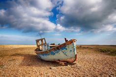 A fishing boat sitting on the beach near the lifeboat station. A stunning place to visit. Discovered by Snappy David at Dungeness Lifeboat Station, Kent, England