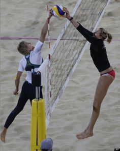 Kerri Walsh of the United States blocks the shot of Australia's Natalie Cook during a beach volleyball match at the 2012 Summer Olympics, Saturday, July 28, 2012, in London.