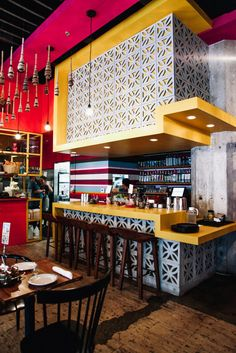 """Fashioned from raw concrete blocks characteristic of the Mexican landscape, this taqueria bar is vertically bordered with a bold yellow """"stepped"""" bar top, a feature inspired by Mayan ruins and tailored specifically to the space. Vibrant colors express vitality and excitement."""