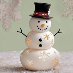 """MR SNOW TEALIGHT HOLDER : Our friendly Frosty warms the heart with his traditional top hat and carrot nose. Snowflake cutouts enhance the glow of a tealight, sold separately, placed inside. Hand-painted porcelain. 7¾""""h. by PartyLite"""