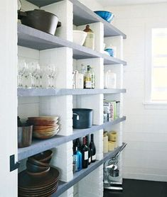 This modern open pantry was built using white painted brick and stained concrete shelves.