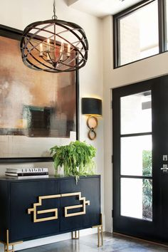 You don't always have to go big to go bold — sometimes, it's the smaller details that command attention. Though the large-scale art and stunning modern pendant draw the eye in this open entryway, the circular forms of the sconces and the bold abstract han Open Entryway, Entryway Decor, Entryway Ideas, Entrance Ideas, Foyer Decorating, Interior Decorating, Interior Design, Decorating Tips, Modern Foyer