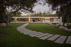Staggered, rectangular concrete pavers create a curved modern path that runs through this contemporary backyard.