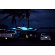 The parking lot of the Ocean Front beach bar in Jobos, Puerto Rico. A warm night breeze and a cold...