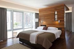 Urban sophistication is at its pinnacle in this modern bedroom where a wall of windows takes in the city view. A wood slab partition wall behind the bed doubles as a headboard and a convenient room divider. House Design, Interior, Apartment Design, Home, Home Bedroom, Bedroom Interior, Modern Bedroom, Interior Design, Interior Design Bedroom