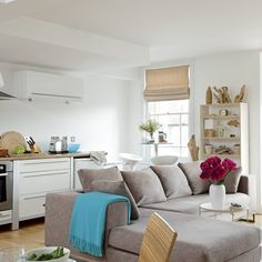 white walls, gray sofa, turquoise accent. Coastal open-plan kitchen