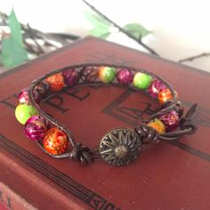 This bracelet is made of acrylic beads red, brown, green, orange, and purple with gold accents between brown smooth leather cording. The closure is a beautiful bronze-colored metal button. Acrylic Beads, Metal Buttons, Earth Tones, Gold Accents, Smooth Leather, Bracelet Watch, Bronze, Closure, Purple