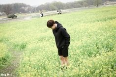 """Here is the Rape flower field in Gyeongju. Among the Rape flowers bloomed yellow BTS flower bloomed. (Sorry for being so cheesy ;;) JIMIN sat down as he has a perfect pose to make at a flower field. JIMIN """"This pose goes along well with a flower field background! (what?)"""""""
