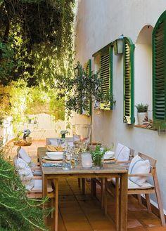 Comedor de verano en un patio rodeado de verde