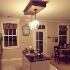 replaced the fluorescent lighting...Kitchen island lighting...pallet wood box made by the hubby! Allen & Roth lighting