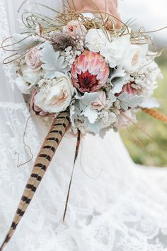 Rustic boho wedding bouquet with Protea, roses, Dusty Miller and feathers | Mallory Sparkles Photography