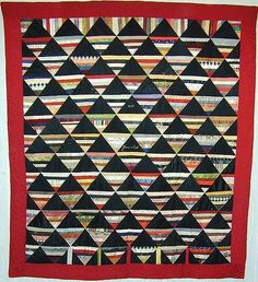 """Roman Stripe Quilt; Dated 1897  This is a rarely seen pattern made more distinctive by the name and date of 1897. Made of silk and satins. Six of the large black triangles have some cracking as well as several of the small strips. They could be stabilized with appropriate netting or left as is. They are not likely to worsen if the quilt is used as a hanging.  Border is beautifully worked with feather quilting. Measures 66"""" x 76""""; signed and dated 1897."""