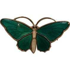 Aksel Holmsen sterling silver buttefrly pin with a white enamel body and green basse taille enamel wings.  The pin measures 1 3/8 x 3/4.  It weighs $46