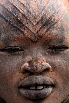 Africa | a close up of a Mundari girl in a cattle camp near Tarakeka; her face has been covered with ocher and ash.  On her forehead are some tribal scarification marks.  Southern Sudan | © Bruno Zanzottera.: