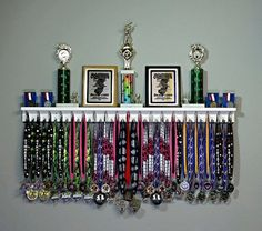 The Premier Award Display Rack for all your hard-earned Award Medals, Trophies, and Plaques! All orders ship within 1-3 business days! All 4 Foot Award Medal Display Racks include: 37 pegs to accommodate Lanyard Ribbon Medals; 3 1/2 Trophy Shelf for Trophy Display; Trophy Shelf includes a Dual Groove design for displaying Cased Pin Medals and/or Plaques; Mounting instructions and 2 wall mounting screws. Satisfaction Guaranteed! If you are not completely satisfied with your produc...