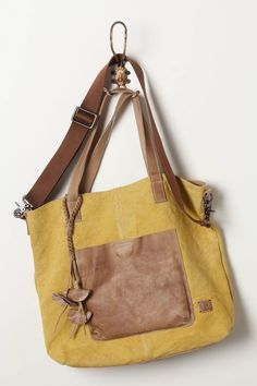 Soft, slouchy and beyond roomy, this faded canvas satchel is fitted with worn leather pockets and straps. By Frye.