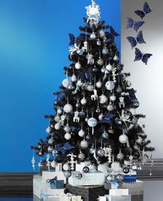 Dark and silver butterfly themed Christmas tree. Be mysterious and elegant with this Christmas tree design featuring butterflies and shiny, sophisticated ornaments.