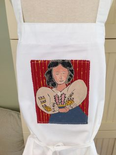 """Hand painted panel sewn on the front of a duck canvas apron (65% Polyster 35% Cotton)  Apron is unisex one size fits all. 32"""" long and 32"""" wide (excluding strap and ties).  To keep painting vibrant, hand wash and avoid washing the panel.  Original, one of a kind item  $25.00"""