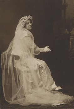 Woman in wedding gown, full-length portrait, seated, facing right