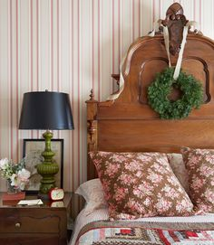 Most of the furnishings, such as the guest bedroom's patchwork quilt and hand-carved bed, are early American antiques. Pops of black (like the lampshade and picture frame) add a touch of contemporary cool to the room's traditional patterns and textures.   - CountryLiving.com