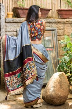 A silk saree in grey, beautifully contrasted by a gold brocade border edged with maroon, paired with a rich Kalamkari blouse. #saree #india #blouse #houseofblouse #wedding