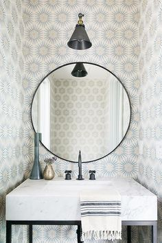 Wonderfully designed powder room is lit by a matte black swing arm sconce fixed to a wall clad in cream and blue sunburst wallpaper above a black round vanity mirror.