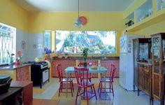 É uma cozinha brasileira com certeza. O fogão a lenha que divide o ambiente, o piso com ladrilho hidráulico e as cores quentes garantem o aconchego do tempo de nossos avós. Criada pela designer de interiores Neza Cesar, tem ainda vista para a horta