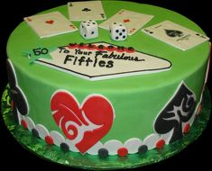 Fabulous 50's Birthday Cake, Green buttercream iced,  round cake decorated in a Las Vegas theme. Hearts, Spades, Clubs, and Diamonds adorn the side of this cake while dice and the Ace card from each suit sits atop. Poker chips and the Las Vegas themed welcome sign complete the look. Everything on this cake is EDIBLE.  (Serves 8-80 party slices)