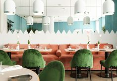 Velvety salmon pink benches and forest green chairs add color and richness to this contemporary restaurant.
