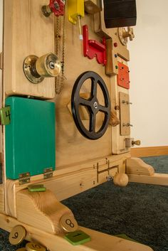 """I built this for my nephew. Has a periscope, steering wheel, shifter, throttle, lock box with coin slot, lights and buzzers, knobs and clickers, """"peek a boo"""" slide. The back side has several doors with easy and challenging latches with family photos behind them. I made wooden nuts and bolts and added male and female plumbing fittings to build his hand eye coordination. Years of fun and learning, #Busyboard, #Kids"""