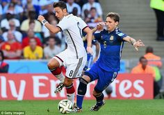 Shadow play: Mesut Ozil tries to evade Argentina midfielder Biglia in the early stages...