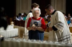 Dolly Robinson, 85, of Richmond, Va., carries a candle during Mass for the feast of the Assumption of Mary Aug. 15 at the Basilica of the National Shrine of the Immaculate Conception in Washington. The feast celebrates the belief that Mary was taken, body and soul, into heaven at the end of her life. (CNS photo/Tyler Orsburn)