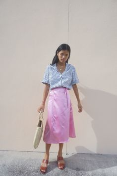 You can always count on being pretty in pink. This satiny wrap skirt is the perfect combination of feminine and chic and looks amazing with the sun shining off of it on warm summer day. Pair with a white tee and matching pink slides.    By  Lisa Says Gah     100% Polyester    Deadstock fab
